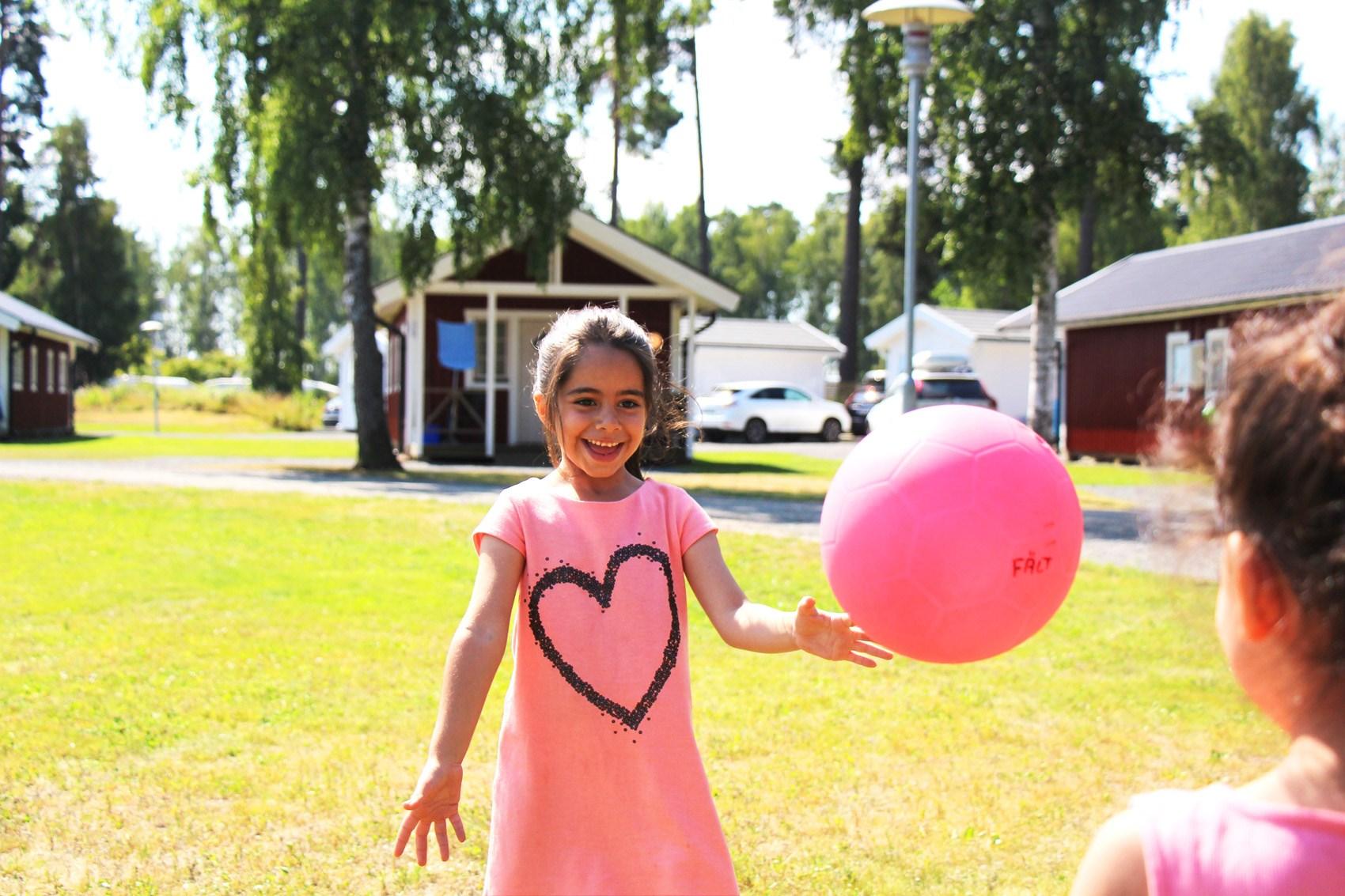 Två unga flickor leker med en boll på campingen